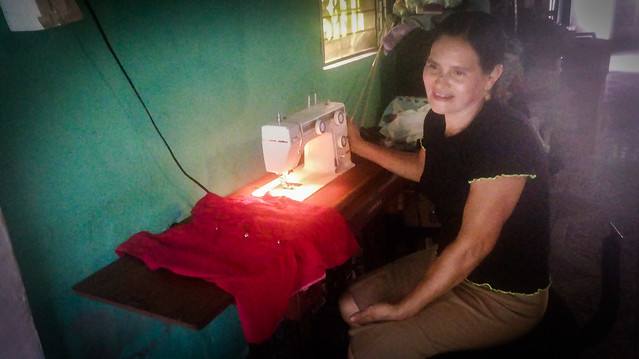 Ermelinda Lobos ante su máquina de coser eléctrica, uno de los beneficios que le trajo la energía producida por la minicentral hidroeléctrica construida en su comunidad, en el noreste salvadoreño. Antes, por falta de electricidad en su caserío, a esta costurera profesional le tocaba coser en una máquina movida a pedal, iluminarse con candiles y planchar con una plancha calentada con carbón. Foto: Edgardo Ayala/IPS
