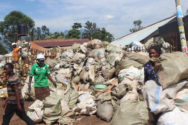 Dos mujeres y algunos hombres recolectan desechos para su reutilización en un basurero al aire libre en Mbale, una ciudad del este de Uganda. El uso ecológico de desechos plásticos o de neumáticos se considera más ecológico que su eliminación o reducción. Foto: Wambi Michael / IPS