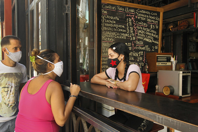 Una empleada atiende a dos clientes en un restaurante que actualmente solo expende alimentos para llevar, en el casco histórico de La Habana Vieja, en Cuba. Una investigación de la consultara Auge reveló que 80 por ciento de los emprendedores cubanos opina que las políticas de Washington hacia Cuba afectaron su negocio. Foto: Jorge Luis Baños/IPS