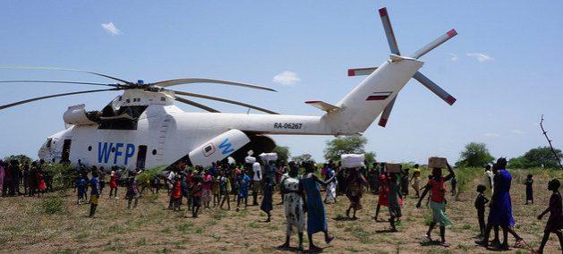 Suministros de emergencia son entregados a la población de una pequeña localidad de Sudán del Sur, tras llegar en un helicóptero del Programa Mundial de Alimentos (PMA). Foto: Peter Martell/Unicef