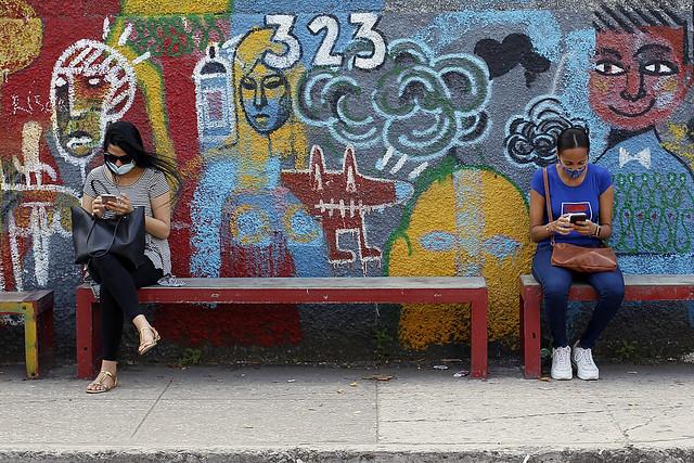 En Cuba, a medida que aumenta el acceso a internet crece también la violencia digital de género, como visibilizan campañas de información sobre el problema y las herramientas de las mujeres para defenderse. En la imagen dos mujeres residentes en La Habana interactúan con sus teléfonos móviles mientras esperan el ómnibus. Foto: Jorge Luis Baños/IPS