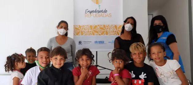 Dos madres venezolanas, participantes en el programa de formación y empleo Empoderando Refugiadas, posan junto a un grupo de niños en Sao Paulo, la principal plaza económica de Brasil. Foto: Miguel Pechioni/Acnur