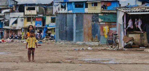 Niños juegan a las afueras de su casa en una barriada de Mumbai, en India, un país donde el cambio climático y la pandemia pueden empujar a millones de personas hacia la extrema pobreza. Foto: Shutterstock/BM