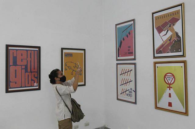 Una joven fotografía con su teléfono móvil algunos carteles que participaron en el concurso sobre la no violencia hacia la mujer, denominado CartelOn, durante el acto de premiación en La Habana. El certamen integró las actividades en Cuba por los 16 días de activismo contra la violencia hacia las mujeres, entre el 25 de noviembre y el 10 de diciembre. Foto: Jorge Luis Baños/IPS