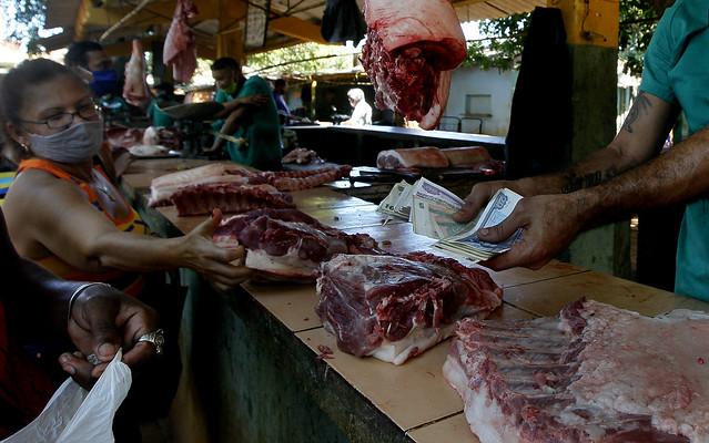 Una clienta señala un corte de carne mientras detrás del mostrador un empleado sostiene un fajo de billetes en CUP y CUC, en un mercado privado de Boyeros, uno de los municipios de La Habana. Desde el 1 de enero, en Cuba circulará únicamente el peso cubano (CUP), con una tasa de cambio de 24 unidades por dólar. Foto: Jorge Luis Baños/IPS