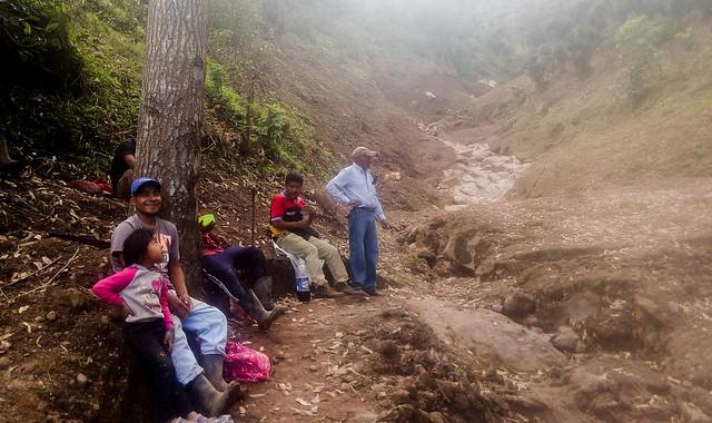 Campesinos se toman un descanso de su trabajo para reabrir un camino cortado por el aluvión que bajó de la cima del Picacho, una montaña adyacente al cráter del volcán de San Salvador. El deslizamiento, el 29 de octubre, provocó la muerte de nueve personas, otra desaparecida y cuantiosos daños materiales. Foto: Edgardo Ayala/IPS