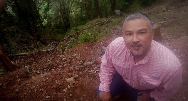 Héctor Velásquez, propietario de la finca cafetalera Los Robles, en una ladera del volcán de San Salvador, muestra un deslizamiento de tierra en su cafetal tras el paso de la tormenta tropical Amanda, en mayo. Con el apoyo del Programa de las Naciones Unidas para el Medio Ambiente, ha innovado sus medidas de prevención, como la introducción de barreras vivas y muertas. Foto: Edgardo Ayala/IPS