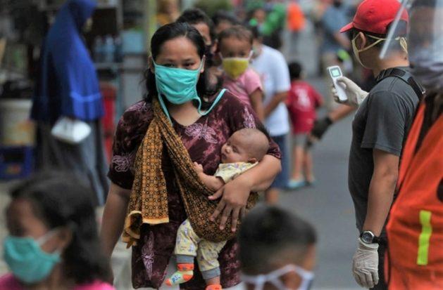 Una madre indonesia camina con sus hijos por una calle. Todos menos el bebe que lleva en brazos portan mascarillas, una protección ante la covid que se universalizó en el mundo en 2020. Foto: Achmad/Banco Mundial