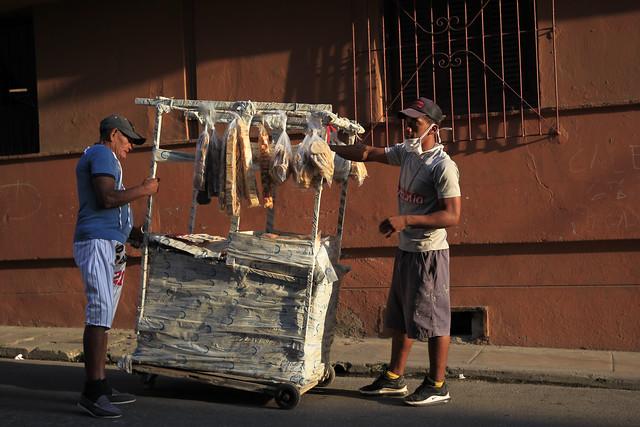 Un vendedor ambulante de panes y galletas atiende a un cliente en su precario puesto en una calle de La Habana, en Cuba. Los confinamientos, el corte de la cadena de suministros y la crisis económica por la pandemia, hundieron los ingresos, sobre todo quienes trabajan en el sector informal, que suelen ser también los más expuestos a la covid, pues no pueden trabajar a distancia o pedir una licencia para proteger su salud. Foto: Jorge Luis Baños/IPS