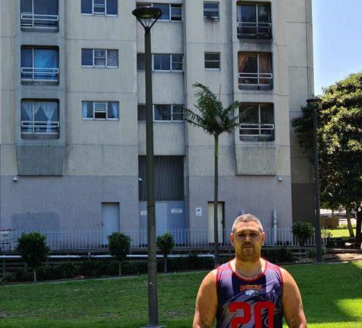 Keenan Mundine, ante uno de los edificios de The Block, un conjunto de viviendas sociales para la comunidad aborigen donde creció en los suburbios de Sídney. El ahora activista utiliza su experiencia por el sistema penal de Australia para promover soluciones creativas para romper el ciclo de violencia, policía y prisiones que sufren de manera desproporcionada y discriminatoria los indígenas del país. Foto: Neena Bhandari / IPS