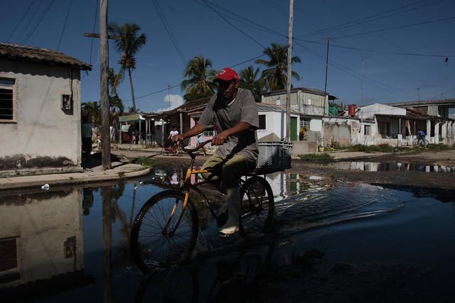 Un ciclista transita por una calle inundada en la localidad de Batabanó, en el sur de la provincia cubana de Mayabeque. La zona se caracteriza por la presencia de zonas costeras bajas y, a menudo cenagosas, proclive a frecuentes inundaciones durante el paso de huracanes e intensas lluvias. Foto: Jorge Luis Baños/IPS