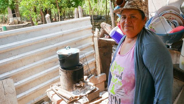 Petrona Cañénguez explica cómo cocina una sopa de frijoles en una de las cocinas eficientemente energéticas, conocidas como fogones rockets, en un habitáculo externo de su vivienda en la el caserío de San Sebastián El Chingo, uno de los beneficiados con un programa de desarrollo sostenible, en el municipio de San Luis La Herradura, en la costa del sur de El Salvador. Foto: Edgardo Ayala /IPS