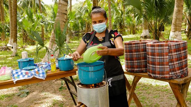 María del Carmen Rodríguez prepara un arroz en un fogón rocket, una estufa que usa unas pocas ramas de madera de una especie que emite menos emisiones de CO2 que el manglar, cuya sostenibilidad se preserva, además. Muchas familias de la comunidad de El Salamar se han beneficiado de estos equipos de gran eficiencia energética, así como otras iniciativas promovidas en el sur de El Salvador, sobre la costa al océano Pacífico. Foto: Edgardo Ayala /IPS
