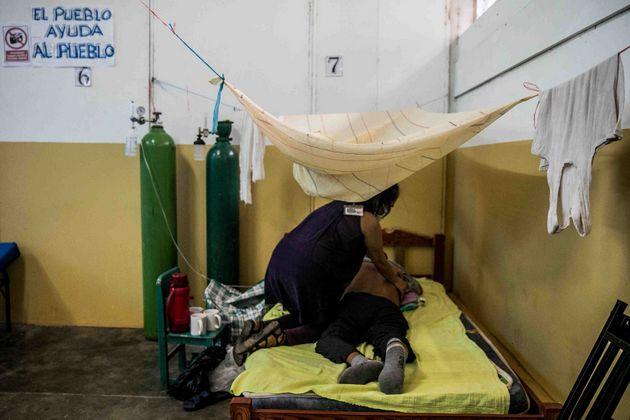 Atención a un enfermo de covid por una integrante del Comando Matico, en la Amazonia peruana. Foto: Sebastián Castañeda /Periodistas por el Planeta