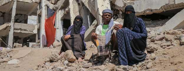 Una familia yemení junto a los escombros del edificio que antes fue su vivienda. Foto: OCHA