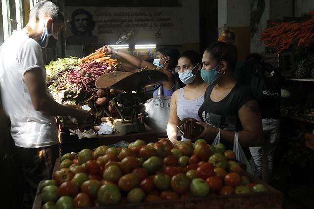 Clientes usan mascarillas protectoras contra el contagio de la covid, mientras adquieren alimentos en el interior de un estatal agromercado, en el municipio Centro Habana, en Cuba. Foto: Jorge Luis Baños/IPS